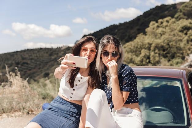 Junge frauen, die auf dem auto aufwirft für selbstporträt sitzen
