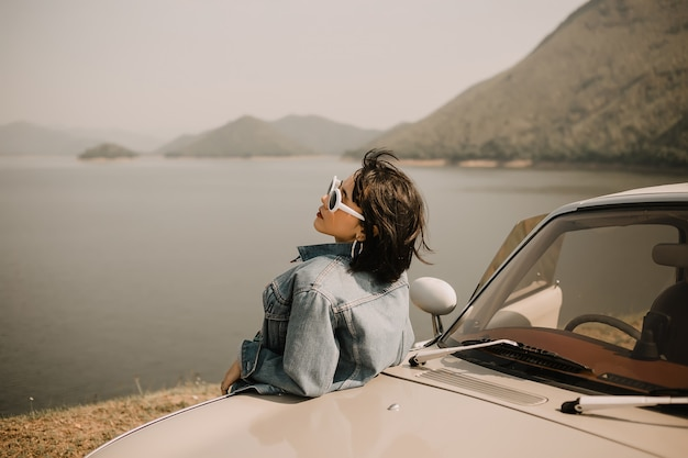 Junge frauen, die auf see sich entspannen. sie fährt mit dem oldtimer zum see. sie trägt eine sonnenbrille.