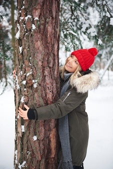 Junge frauen, die baum im winterwald umarmen
