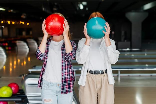 Junge frauen, die bunte bowlingspielkugeln anhalten