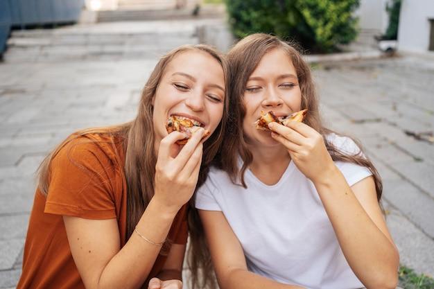 Junge frauen, die draußen zusammen pizza essen