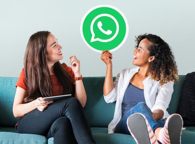 Junge frauen, die eine whatsapp-botenikone zeigen