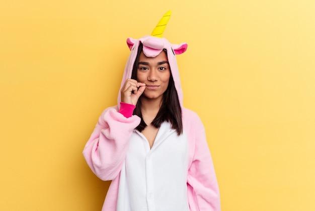 Junge frauen, die einen einhorn-pyjama tragen, isoliert mit den fingern auf den lippen