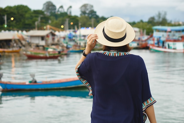 Junge frauen, die einen hut, reiserucksack tragen ansicht des fischereihafens