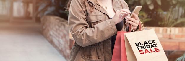 Junge frauen, die einkaufstaschen tragen und online kaufen