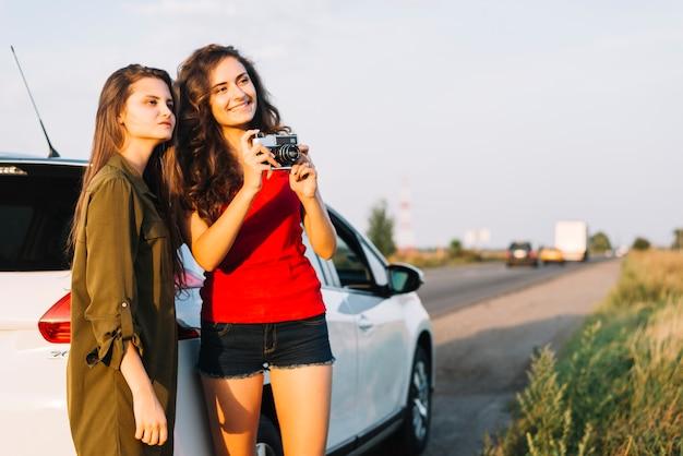 Junge frauen, die fotos mit kamera machen