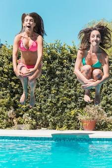 Junge frauen, die in swimmingpool springen