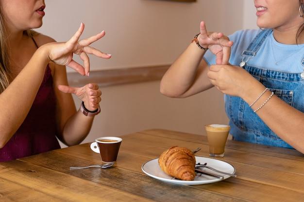Junge frauen, die kaffee trinken und in gebärdensprache sprechen
