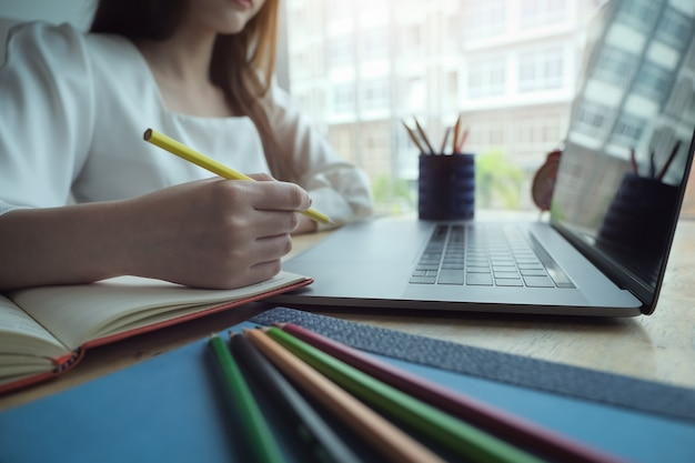 Junge frauen, die mit farbbleistift und -notizbuch arbeiten