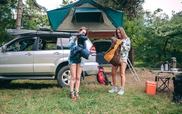 Junge frauen, die mit ihrem fahrzeug schlafsäcke auf dem campingplatz öffnen