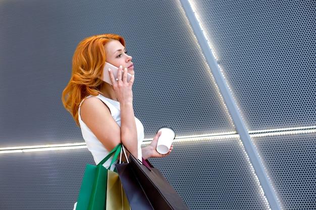 Junge frauen, die mit paketen, die in der modernen mall einkaufen, am telefon sprechen