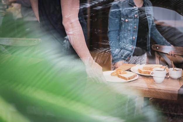 Junge frauen, die morgens frühstück, kaffee und toast mit butter und stau an einem restaurant in japan haben.