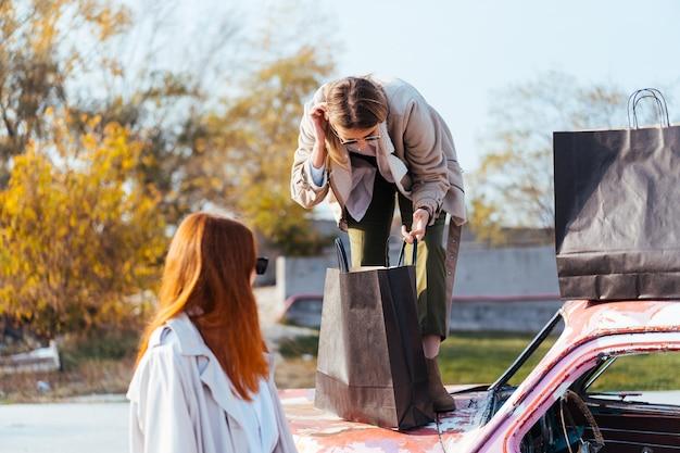Junge frauen, die nahe einem alten geschmückten auto aufwerfen