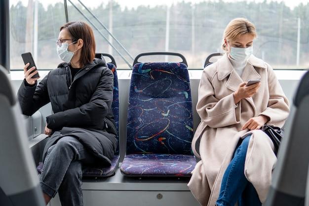 Junge frauen, die öffentliche verkehrsmittel mit chirurgischer maske benutzen