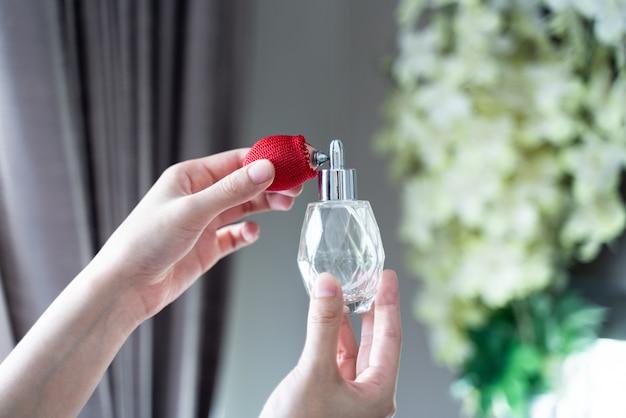 Junge frauen, die parfüm sprühen