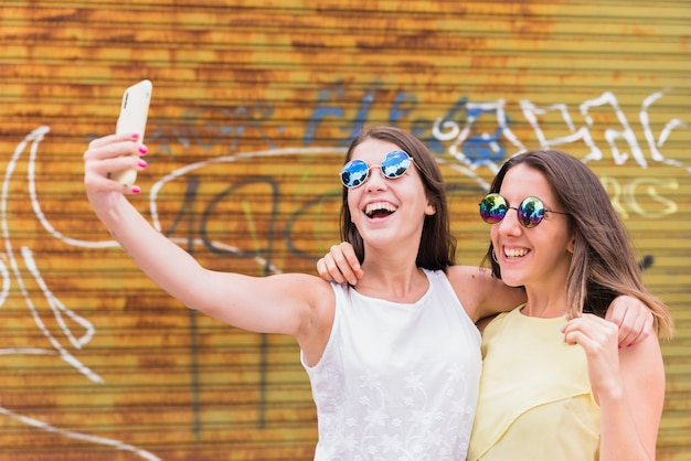 Junge frauen, die selfie auf smartphone nehmen