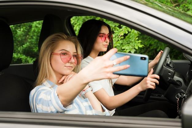 Junge frauen, die selfie im auto nehmen