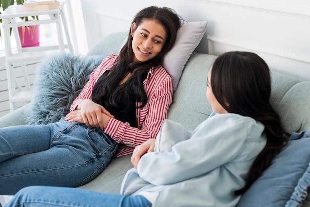 Junge frauen, die sitzend auf sofa sprechen