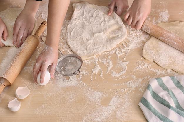 Junge frauen, die teig für gebäck auf küchentisch vorbereiten preparing