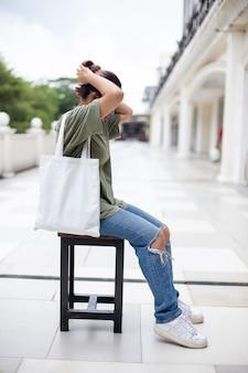Junge frauen, die weiße einkaufstasche halten
