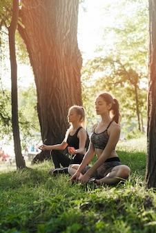 Junge frauen, die yoga im park tun