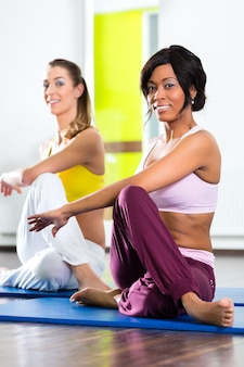 Junge frauen, die yoga und meditation im fitnessstudio für bessere fitness-, kaukasier- und latina-leute tun