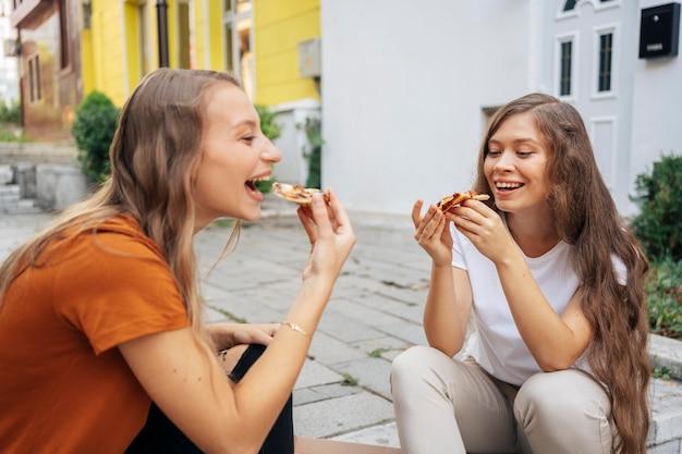 Junge frauen essen pizza zusammen im freien
