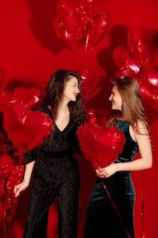 Junge frauen feiern mit herzförmigen luftballons zum valentinstag