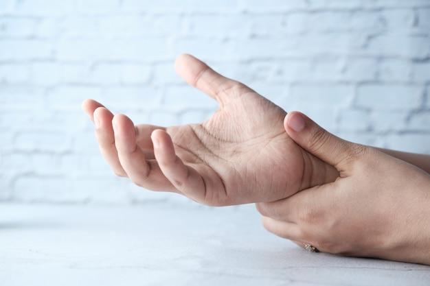 Junge frauen hände auf tisch in leidenden schmerzen am handgelenk, nahaufnahme