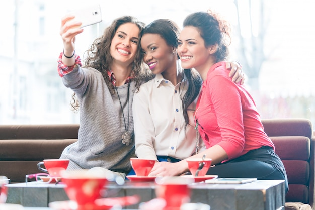 Junge frauen im café, das selfie nimmt