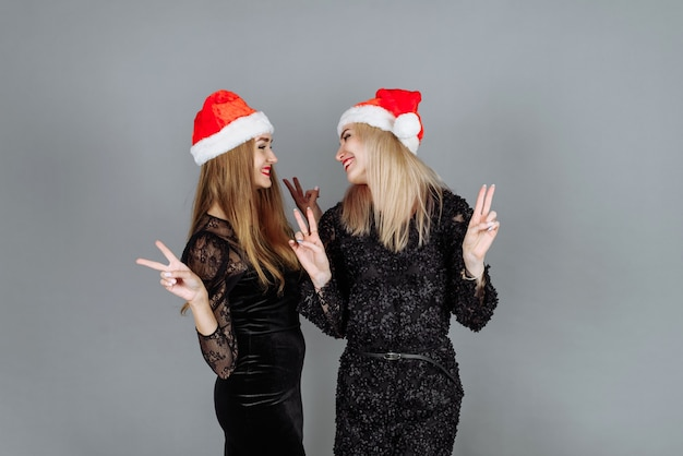 Junge frauen in schwarzen kleidern und weihnachtsmützen