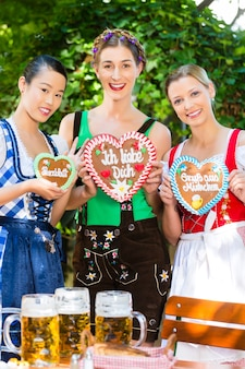 Junge frauen in traditioneller bayerischer kleidung oder tracht mit einem lebkuchen-souvenirherz im biergarten am oktoberfest