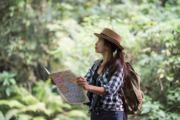 Junge frauen menschen wandern mit freunden rucksäcke gehen zusammen und suchen karte und fotografieren