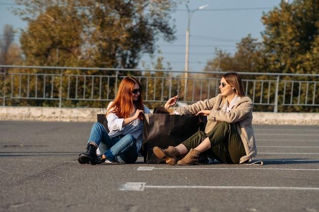 Junge frauen mit einkaufstüten sitzen auf dem parkplatz
