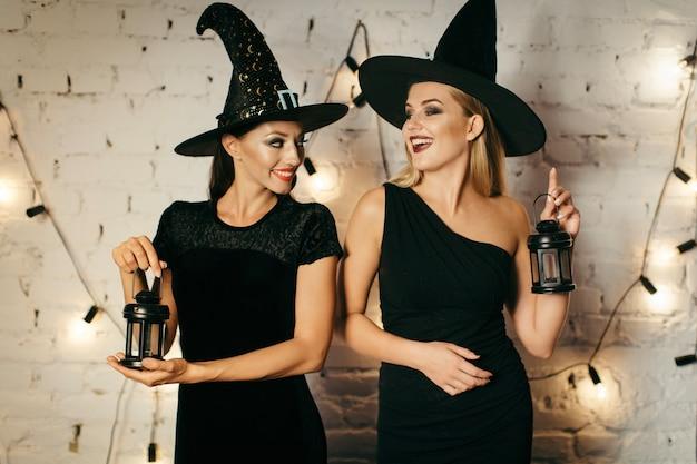 Junge frauen mit laternen in halloween kostümen