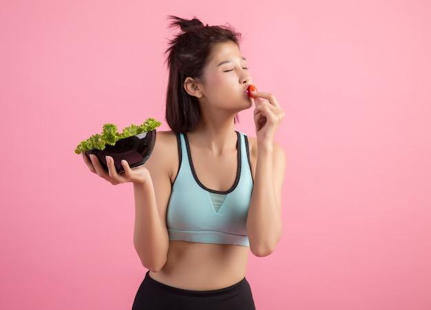 Junge frauen mögen gemüse auf einem rosa essen.