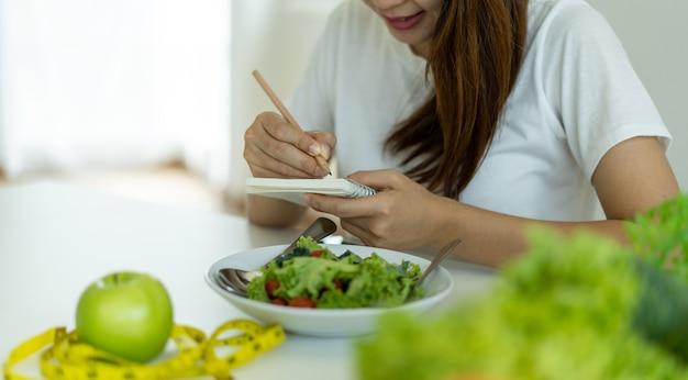Junge frauen planen mahlzeiten während des gewichtsverlusts. frauen im gesundheitswesen wählen keto.