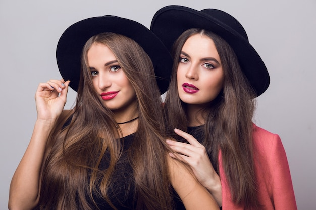 Junge frauen posieren und tragen stilvolle schwarze hüte