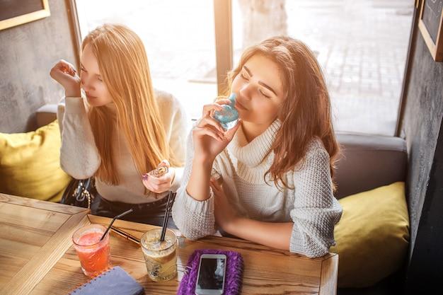 Junge frauen sitzen am tisch und riechen parfüm
