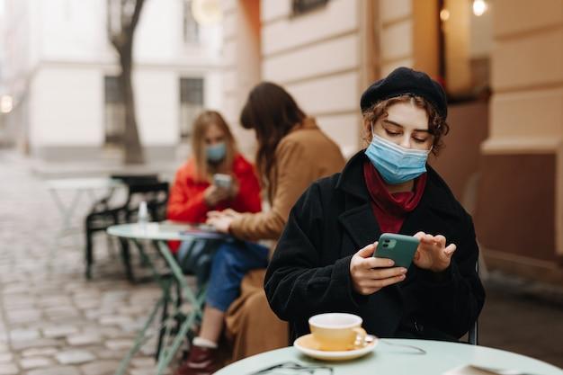 Junge frauen sitzen auf offener caféterrasse in medizinischen hygienemasken und verwenden moderne geräte. soziale distanz und schutz vor krankheiten.