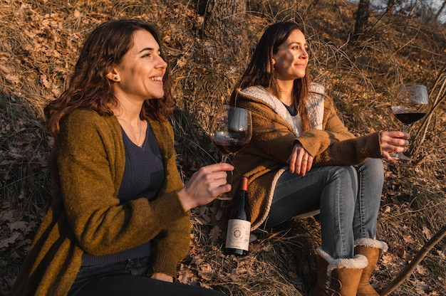 Junge frauen sitzen in einem wald, der den sonnenuntergang beim trinken von rotwein betrachtet. freundschafts-, zusammengehörigkeitskonzept.