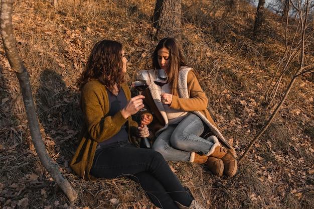 Junge frauen sitzen in einem wald, der zusammen spricht, während er rotwein trinkt. freundschafts-, zusammengehörigkeitskonzept.