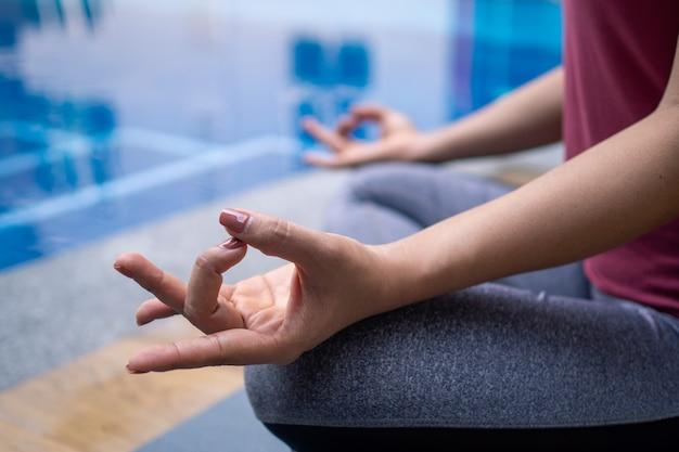 Junge frauen tragen moderne sportanzüge, meditieren, machen yoga, entspannen sich und sitzen bequem am pool. übung im häuslichen und privaten bereich. gesundes lebensstilkonzept