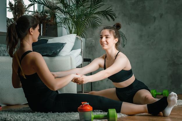 Junge frauen treiben zu hause sport und trainieren online