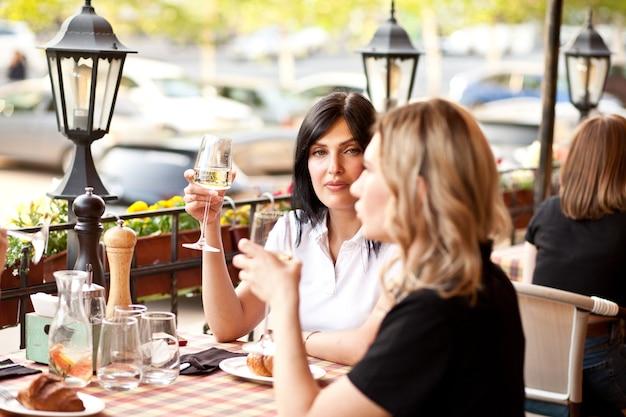 Junge frauen trinken einen weißwein in einer café-terrasse.