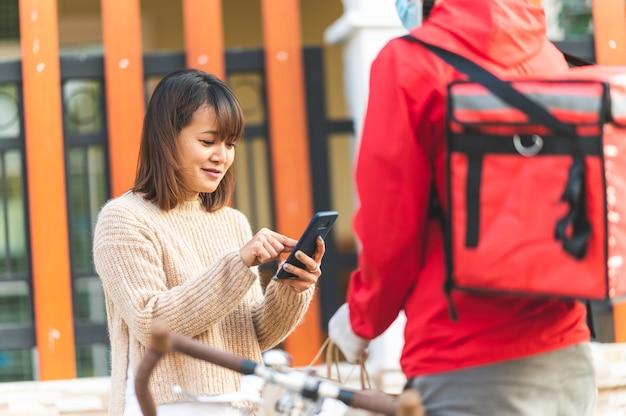 Junge frauen unterschreiben, um die waren über das smartphone-kurierdienstkonzept abzuholen