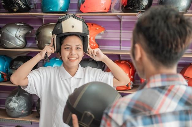 Junge frauen wählen einen helm und tragen ihn, wenn sie von einem verkäufer in einem helmgeschäft bedient werden