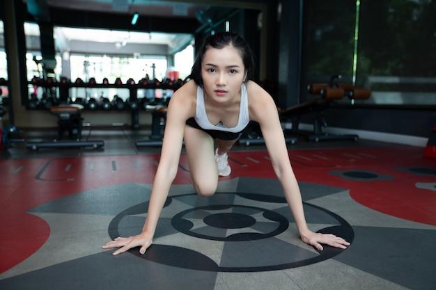 Junge frauen wärmen sich vor dem training auf, indem sie den boden drücken und im fitnessstudio die knie beugen.