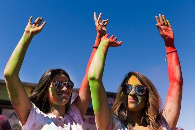Junge frauen, welche die sonnenbrille genießt das holi festival gegen blauen himmel tragen