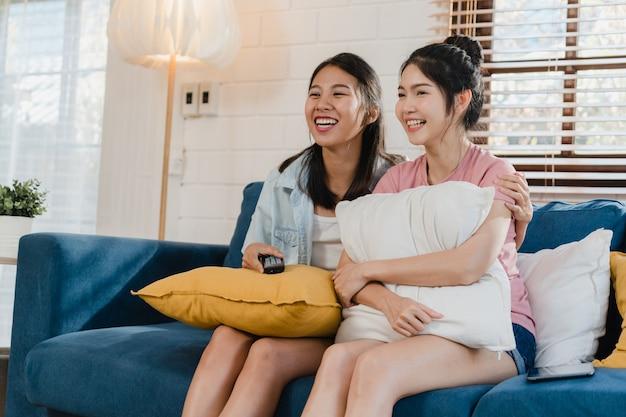 Junge frauenpaare asiens lesbische lgbtq, die zu hause fernsehen